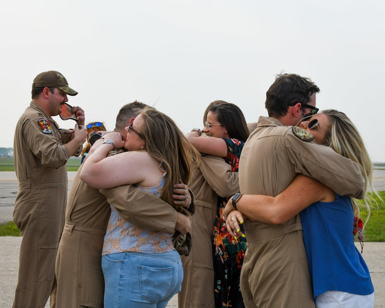 spouses hug their loved ones as they return from deployment