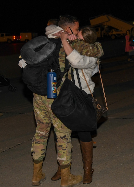A spouse hugs her spouse as he returns from deployment