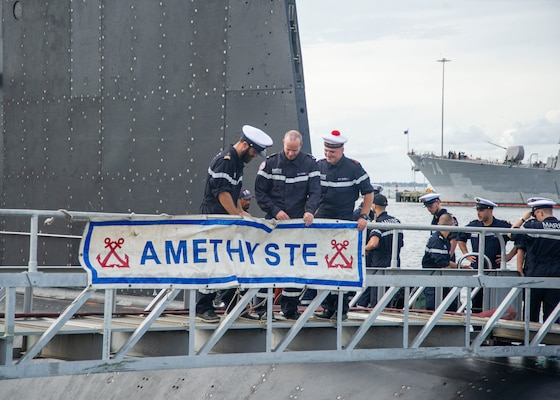 Crewmembers assigned to the French submarine FNS Améthyste (S605) place the boat's banner as it moors pier side at Naval Station Norfolk, Sept. 16, 2021.