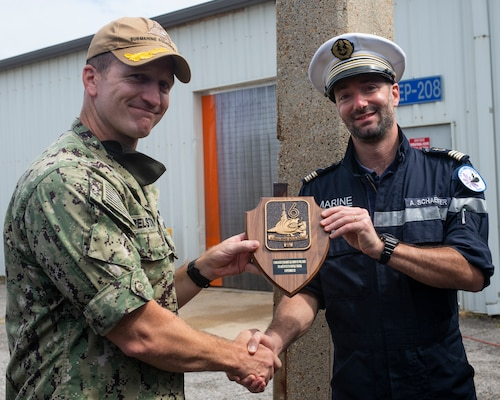 Capt. Jeremy Pelstring, assigned to Commander, Submarine Squadron 6, exchange gifts with Cmdr. Aymeric Schaeffer, commanding officer of the nuclear-powered French submarine FNS Amethyste (S605), at Naval Station Norfolk, Sept. 17, 2021.