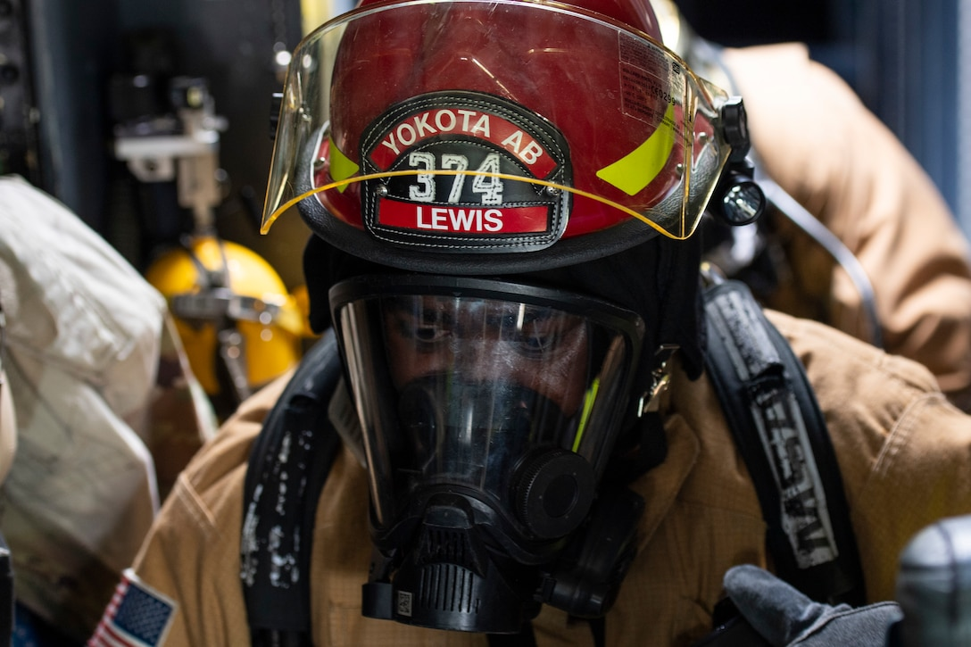 Close-up of a firefighter wearing a red helmet and respirator mask