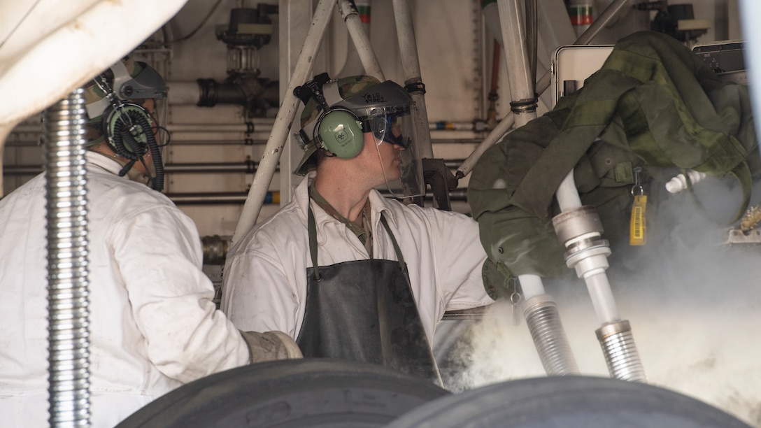 Two Airmen in white coveralls and protective face shields refilling a nitrogen tank