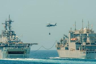 USNS Wally Schirra (T-AKE 8), right, replenishes USS Essex (LHD 2) in the Arabian Gulf.