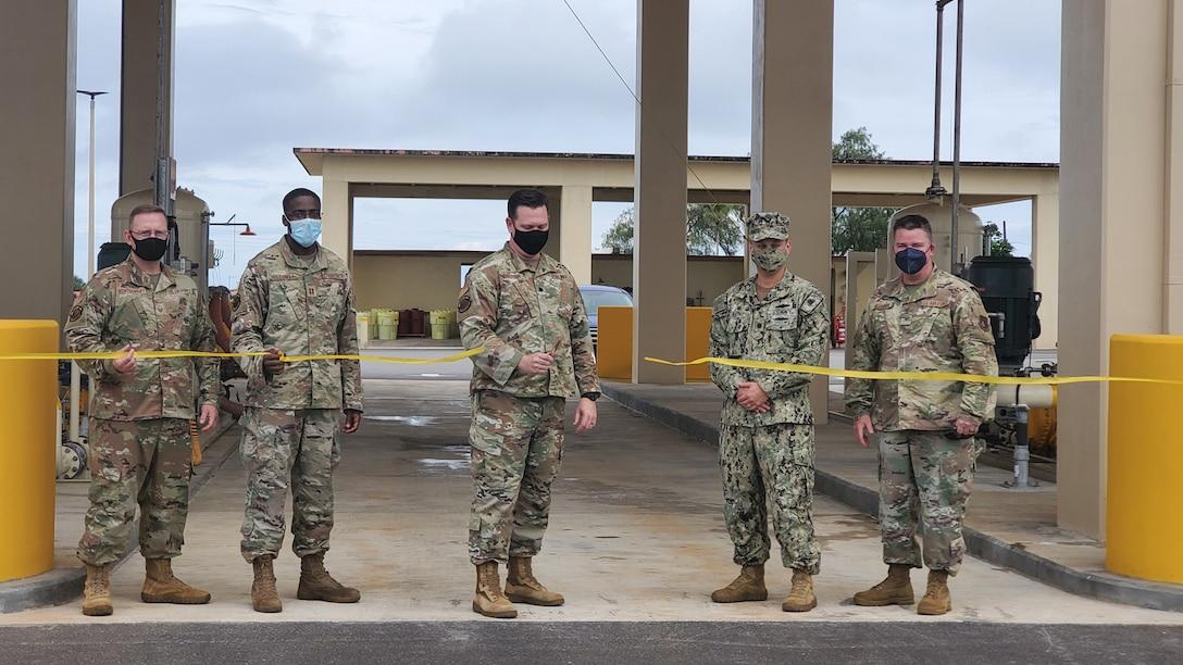 five military members in uniform cut a ribbon
