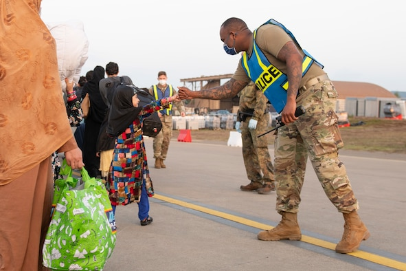 U.S. Air Force Tech. Sgt. Raymond Duesbury, right, 423rd Security Forces Squadron antiterrorism officer assigned to Royal Air Force Alconbury, England, greets a child during Operation Allies Refuge at Ramstein Air Base, Germany, Aug. 31, 2021. Operation Allies Refuge is providing support to evacuees from Afghanistan in the form of food, medical services, and temporary lodging while they await transportation to other transient locations. Ramstein Air Base transformed into U.S. European Command's primary evacuation hub, supporting one of the largest, most complex humanitarian airlift operations in history. (U.S. Air Force photo by Senior Airman Jennifer Zima)