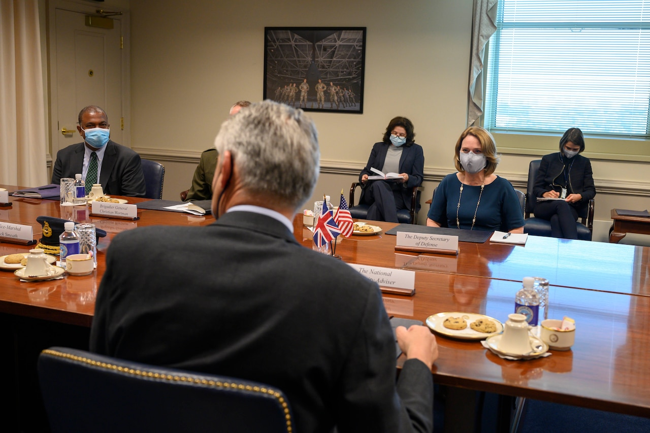 Men and women are seated at a conference table.