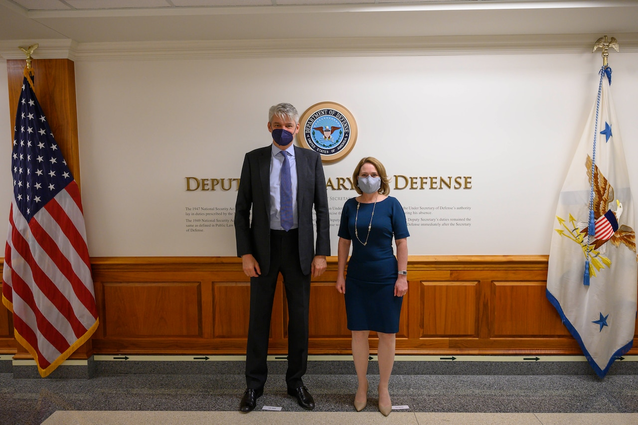 A man and a woman stand in a lobby. The signage on the wall behind them indicates that they are at the Department of Defense.