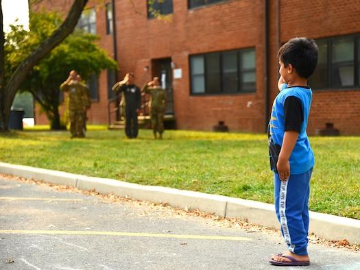 A boy salutes U.S. Troops.