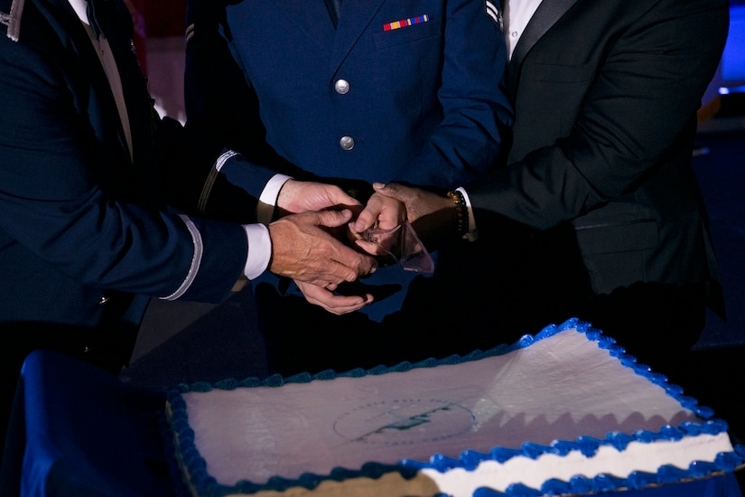 U.S. Air Force Col. Adam Willis (left), Airman 1st Class Seth Grey (middle), and retired U.S. Army Command Sgt. Maj. Patrick Alston, ceremoniously cut the cake aboard the USS YORKTOWN at Patriot's Point, Mount Pleasant, South Carolina, Sept. 17, 2021. During the ball the youngest and oldest in attendance cut the cake together to symbolize the heritage passed between generations.