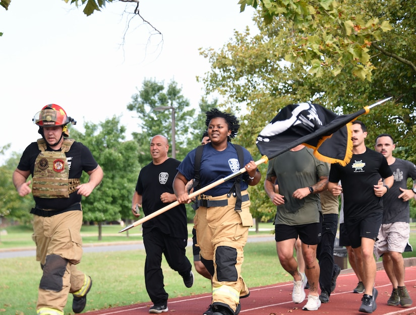 Firefighter runs around the track with POW/MIA flag.