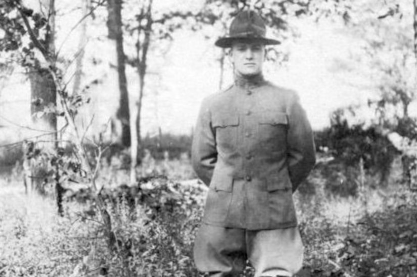 A soldier in World War I-era combat gear stands at ease in a wooded area.