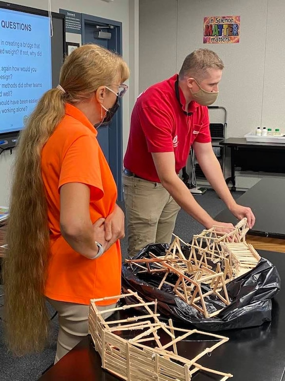 TAM civil engineer Garrison Myer points out the benefits of examining what happened after testing and improving your design for future efforts. All the students now know that the triangle is better for holding weight than rectangles.