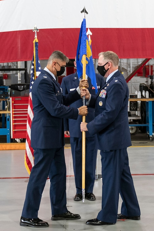 Col. Glenn Collins, 932nd Airlift Wing commander, passes the 932nd Operations Group guidon to Lt. Col. Daniel Davis, 932nd Airlift Wing, incoming Ops Group commander, during the 932nd Operations Group assumption of command ceremony, Scott Air Force Base, Illinois, Sept. 11, 2021. Davis joins the 932nd Ops Group from Tanker/Operations Support Airlift Requirements Office of the Air Force Reserve, Headquarters, where he served as the chief. (U.S. Air Force Photo by Staff Sgt. Brooke Spenner)
