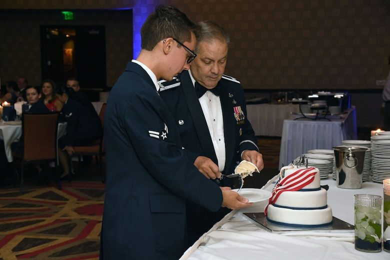 U.S. Air Force Retired Col. Randy Newcome and Airman 1st Class Josh Lentz, 81st Training Support Squadron command support staff, participate in a cake cutting ceremony during the Keesler Air Force Ball inside the Golden Nugget Casino, Biloxi, Mississippi, Sept. 18, 2021. The event, which celebrated the Air Force's 74th birthday, also included a POW/MIA table ceremony. (U.S. Air Force photo by Kemberly Groue)