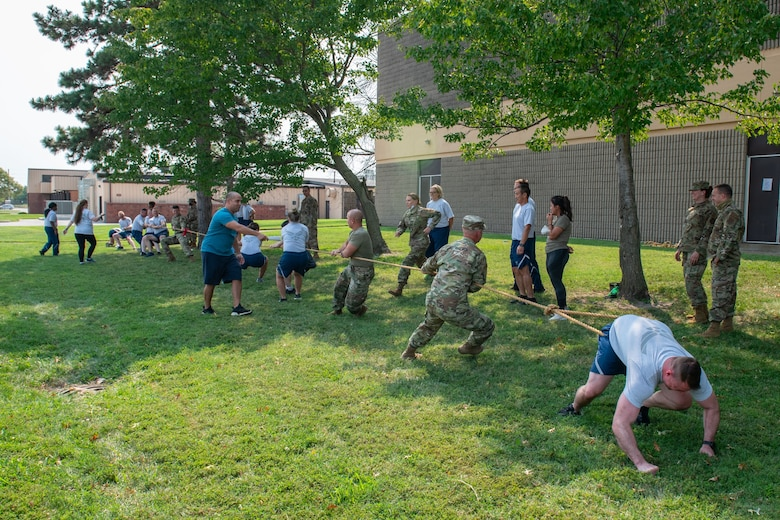 Members of the 932nd Medical Group participate in the tug of war activity during their annual sexual assault prevention and response/suicide prevention training, Scott Air Force Base, Illinois, Sept. 12, 2021. Each activity reviewed the training material, for example during the fit to fight activity a team of airman would be asked a training question and if answered correctly all other groups would do an exercise. (U.S. Air Force Photo by Staff Sgt. Brooke Spenner)