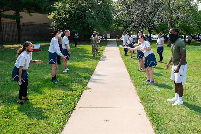 Members of the 932nd Medical Group participate in the water balloon toss activity during their annual sexual assault prevention and response/suicide prevention training, Scott Air Force Base, Illinois, Sept. 12, 2021. Each activity reviewed the training material, for example during the fit to fight activity a team of airman would be asked a training question and if answered correctly all other groups would do an exercise. (U.S. Air Force Photo by Staff Sgt. Brooke Spenner)