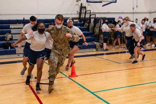 Members of the 932nd Medical Group participate in the three legged race activity during their annual sexual assault prevention and response/suicide prevention training, Scott Air Force Base, Illinois, Sept. 12, 2021. Each activity reviewed the training material, for example during the fit to fight activity a team of airman would be asked a training question and if answered correctly all other groups would do an exercise. (U.S. Air Force Photo by Staff Sgt. Brooke Spenner)