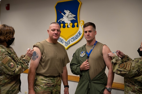 Chief Master Sgt. Justin Apticar, 51st Fighter Wing command chief (left), and Col. Joshua Wood, 51st Fighter Wing commander, receive their flu shots