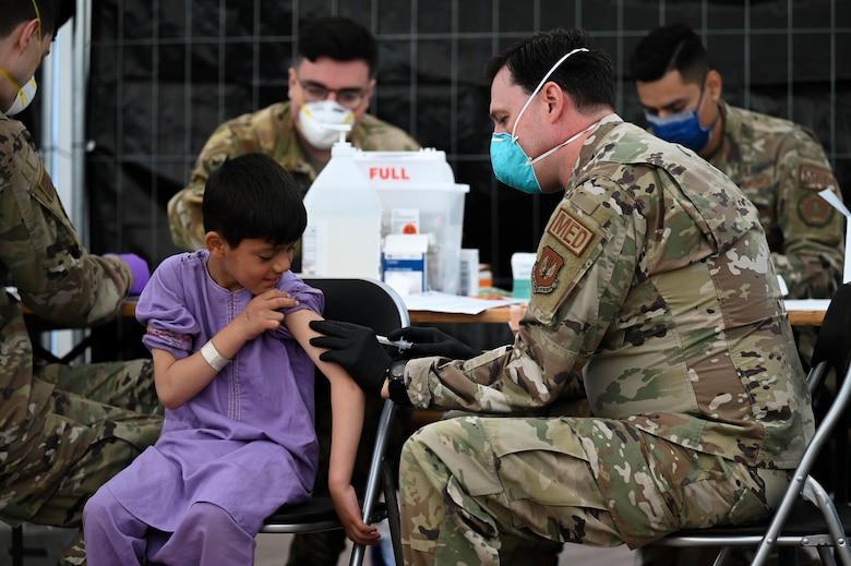 Airman administers MMR vaccine to evacuee.