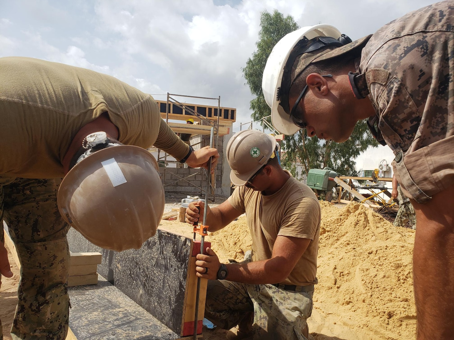 Steelworker Constructionman Rusty Garza and Builder Constructionman Kai Zanjanipour from NMCB 11 work with First Soldier Daji Oussama of the Tunisian Engineers to set concrete formwork for the building foundation.