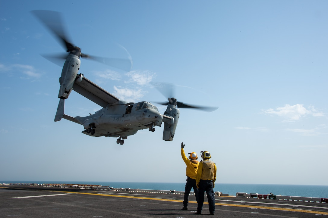 ARABIAN GULF (September 19, 2021) Aviation Boatswain's Mate (Handling) 3rd Class Chad Kihoi signals to an MV-22B Osprey attached to Marine Medium Tilt-Rotor Squadron (VMM) 165 (Reinforced), 11th Marine Expeditionary Unit (MEU), aboard the amphibious assault ship USS Essex, Sept. 19. Essex and the 11th Marine Expeditionary Unit are deployed to the U.S. 5th Fleet area of operations in support of naval operations to ensure maritime stability and security in the Central Region, connecting the Mediterranean and the Pacific through the western Indian Ocean and three strategic choke points. (U.S. Navy photo by Mass Communication Specialist 3rd Class Isaak Martinez)