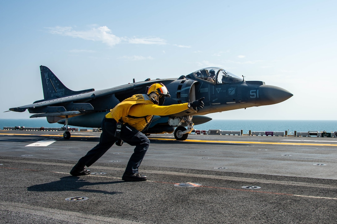 ARABIAN GULF (September 19, 2021) Aviation Boatswain's Mate (Handling) 1st Class Martre Gober signals to an AV-8B Harrier attached to Marine Attack Squadron (VMA) 214 lands on the flight deck of the amphibious assault ship USS Essex, Sept. 19. Essex and the 11th Marine Expeditionary Unit are deployed to the U.S. 5th Fleet area of operations in support of naval operations to ensure maritime stability and security in the Central Region, connecting the Mediterranean and the Pacific through the western Indian Ocean and three strategic choke points. (U.S. Navy photo by Mass Communication Specialist 3rd Class Isaak Martinez)