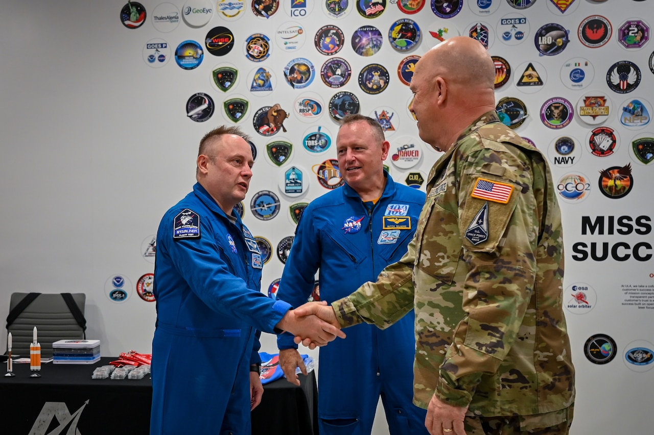General shakes hand with astronaut.