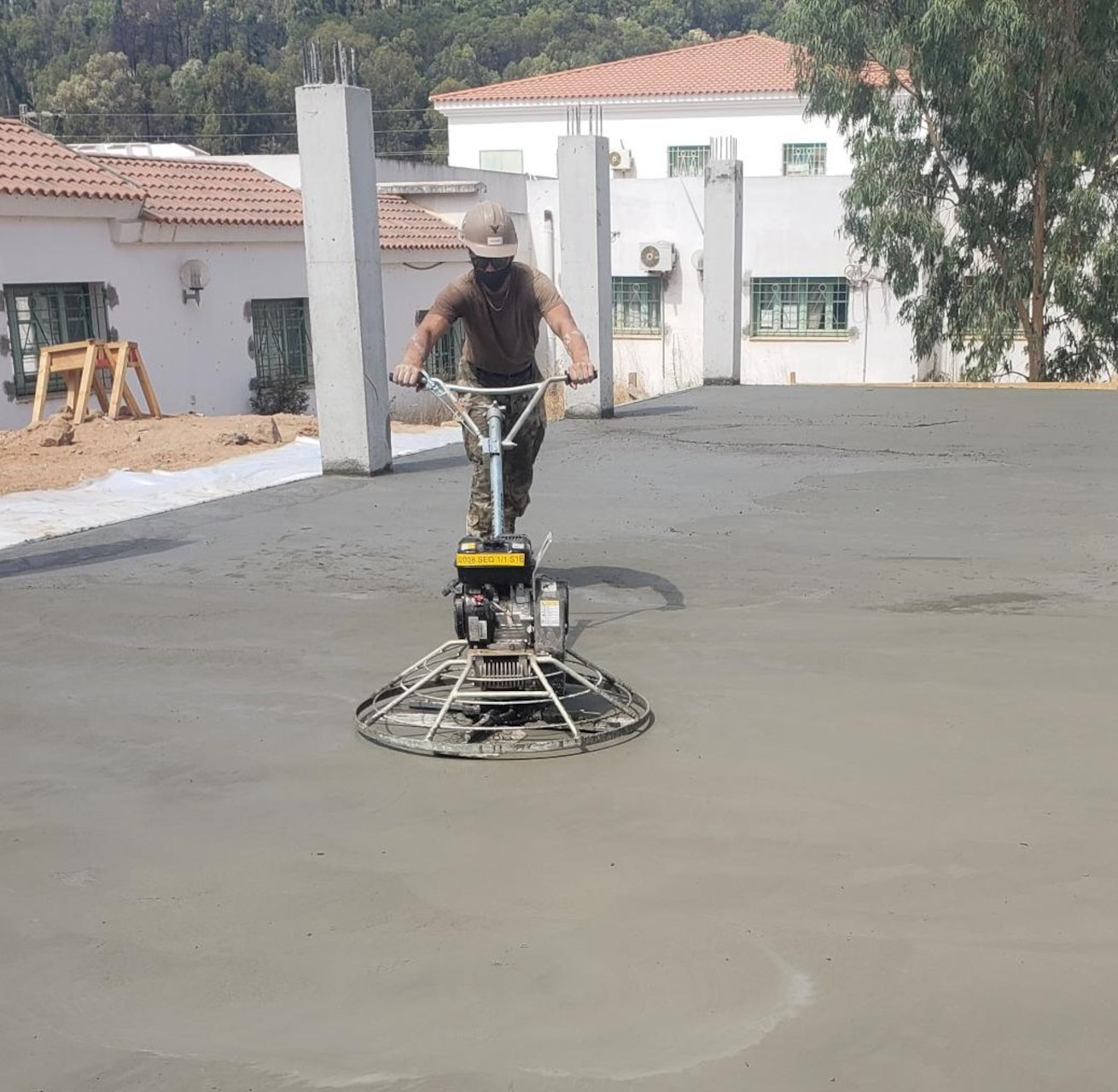 Builder Constructionman 3rd Class Rylee McGuire from Naval Mobile Construction Battalion 11, finishes the concrete floor slab in Tabarka, Tunisia, Aug. 18, 2021.
