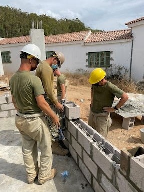 Construction Electrician 3rd Class Paulina Ayala from Naval Mobile Construction Battalion 11 assists with the placement of the concrete floor for the new building in Tabarka, Tunisia, Aug. 18, 2021