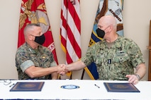 """U.S. Marine Corps Lt. Gen. Robert F. Hedelund, commander, Fleet Marine Corps Atlantic, and Adm. Christopher W. Grady, commander, U.S. Fleet Forces Command, shake hands following the signing of the Naval Integration Campaign Plan (NICP) Sept. 20 in the Rotunda at U.S. Fleet Forces Command. The NICP is a progressive step in operationalizing the Commandant's Planning Guidance, A Design for Maintaining Superiority, and Advantage at Sea. The plan will ensure """"One Fight, One Navy"""" force global posture. U.S. Navy Photo by Chief Mass Communication Specialist Mary Popejoy/RELEASED"""