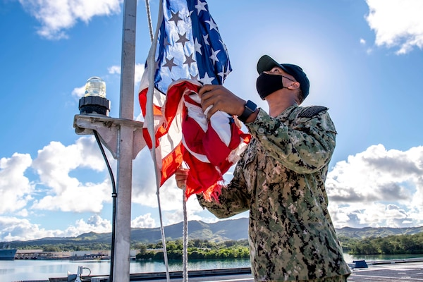 Culinary Specialist Seaman Apprentice Jeremy Reynolds, from Atlanta, hoists the ensign during morning colors aboard the Independence-variant littoral combat ship USS Charleston (LCS 18).