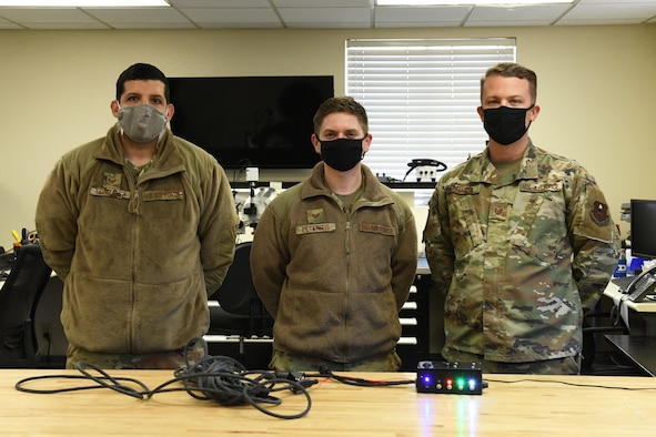 U.S. Air Force Tech. Sgt. Jonathan Gonzalez, left, and Staff Sgt. Gary Peteritis, center, both 56th Maintenance Group Air Force Repair and Enhancement Program technicians, stand with Tech. Sgt. Brady Flynn, right, 56th MXG Continuous Improvement and Innovation manager, to showcase the first prototype of the F-35A Lightning II communication cable rebuild and class tester box February 5, 2021, at Luke Air Force Base, Arizona. The development of the tester box has improved communication between pilots and maintainers on the flight line by allowing Airmen to rebuild F-35 communication cables at the unit level. This is one of many initiatives that advances the 56th MXG CII office's mission to find errors, fix problems and empower the future of the 56th Fighter Wing. (U.S. Air Force photo by Tech. Sgt. Amber Carter)
