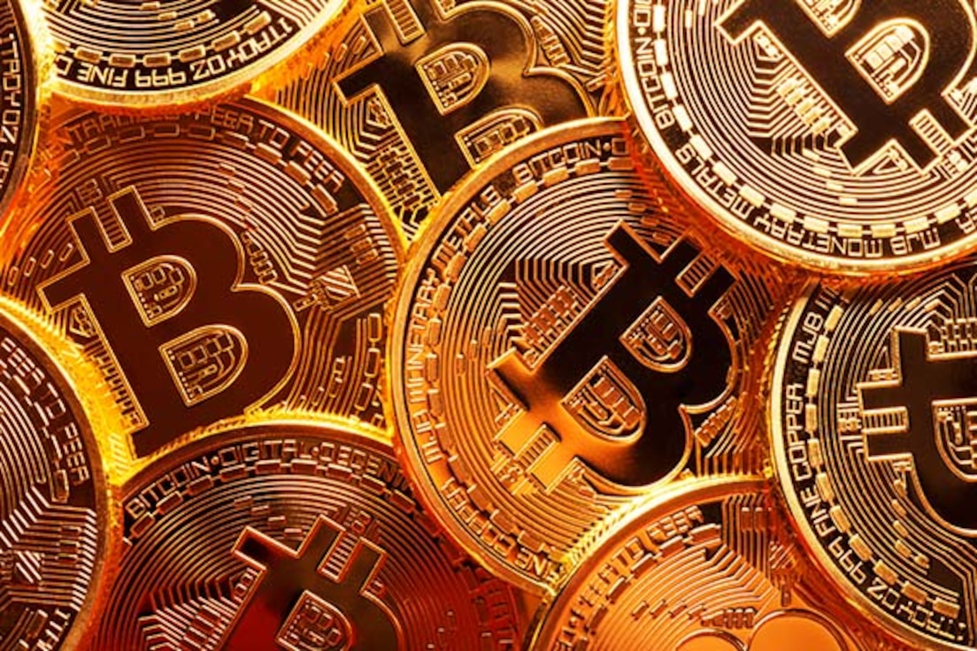 Close-up photo of several gold plated bitcoins together symbolizing the bitcoin market.