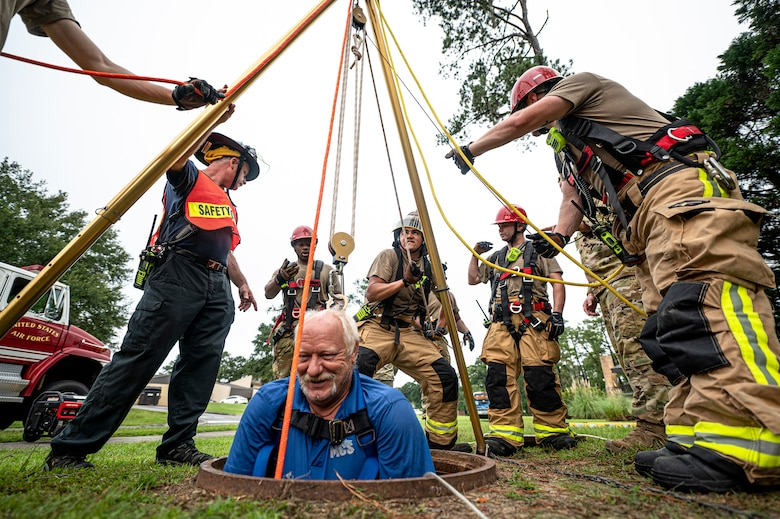 Photo of firefighters using a pulley system to raise an individual from a manhole