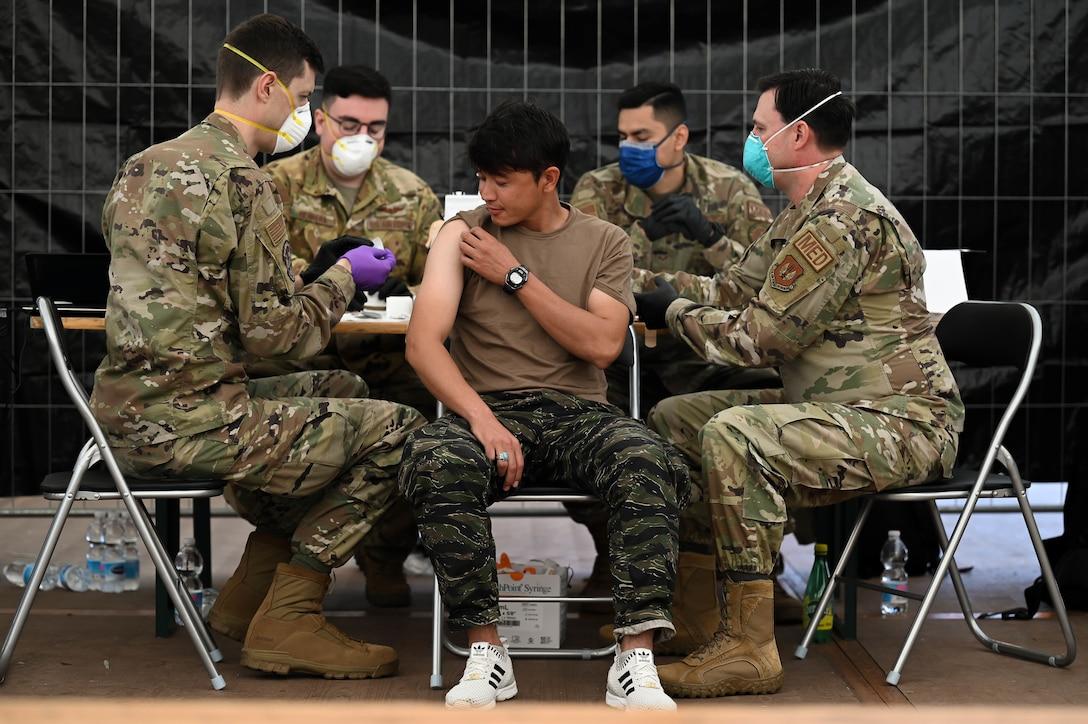 Airmen administer MMR vaccines to evacuee.