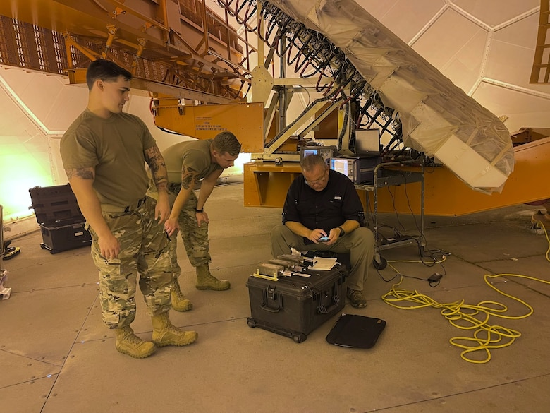 Two U.S. Airmen stand and man sits working on computer