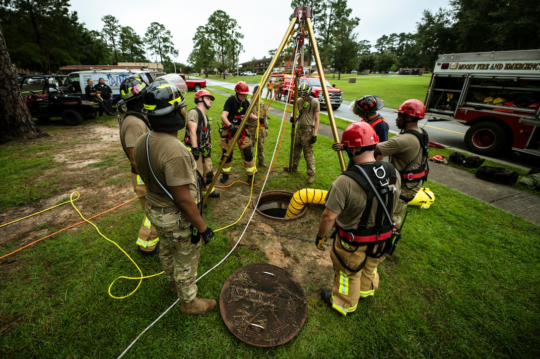 Photo of a group of firefighters standing around a manhole