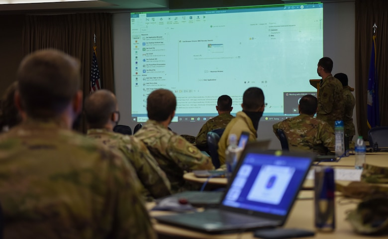 Airmen and Guardians watch as an airman presents their bot the the group.
