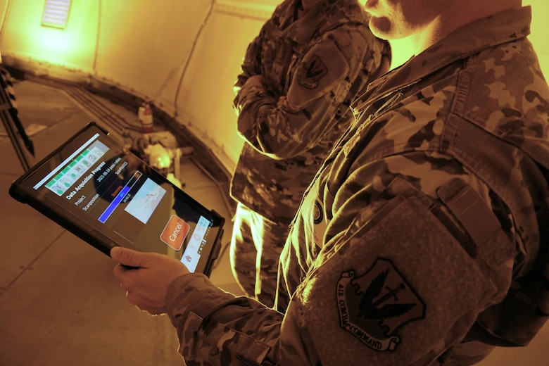 Photo of two U.S. Airmen one holding an electronic device
