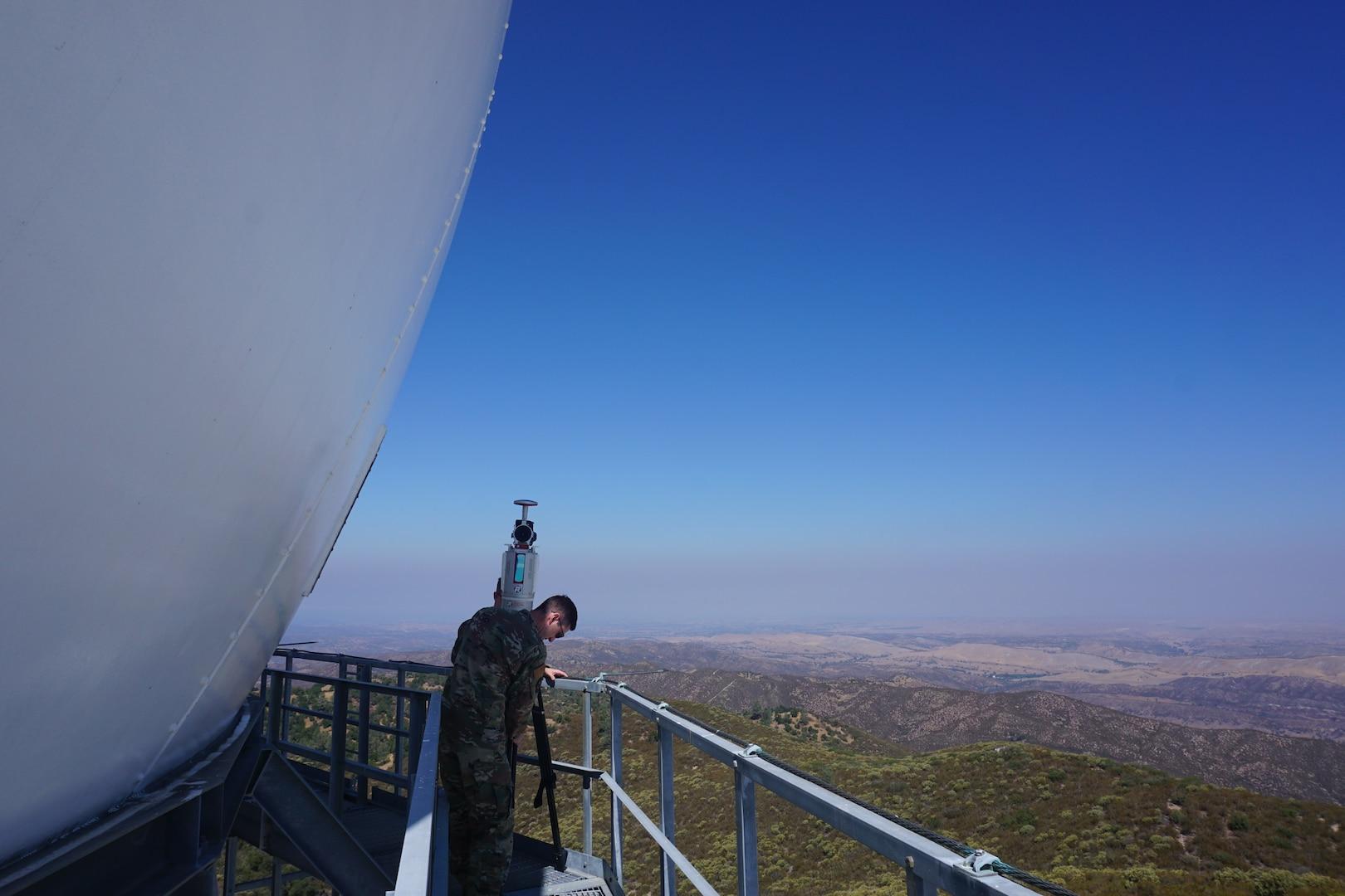 Two U.S. Airmen standing on railing around radar