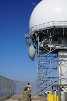 U.S. Airman standing in from of long range radar