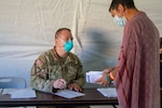 Indiana National Guard Sgt. 1st Class Joseph Stringer interprets for an Afghan guest during medical screening, Friday, Sept. 10, 2021, at Camp Atterbury in Indiana. Task Force Atterbury, consisting of active-duty and National Guard service members supporting this federal mission, will provide housing, medical, logistics, and transportation for the Afghan evacuees.