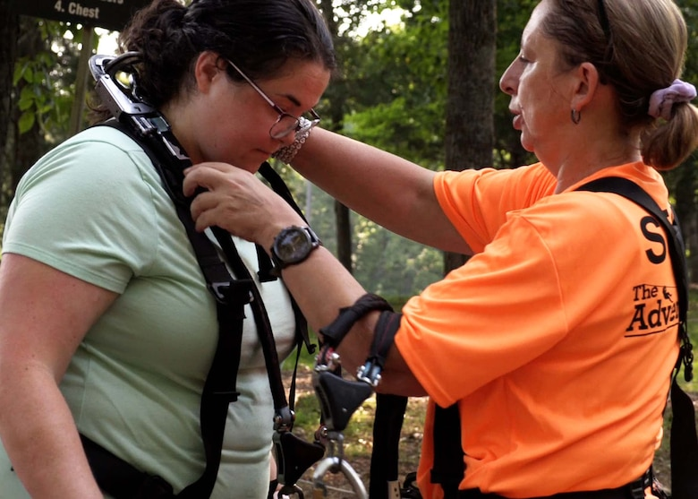 U. S. Army Corps of Engineers Nashville District Project Manager Dana Sexton has her harness adjusted by one of the staff at the Adventure Park in Nashville, Tennessee, before she scales the ropes course as one of her final challenges during the LDP II course.