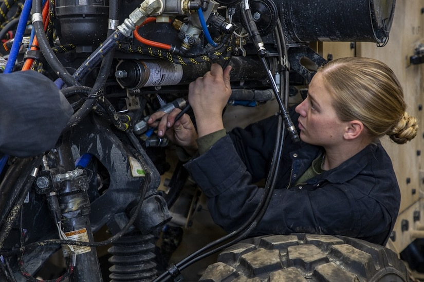 A service member works on a vehicle.