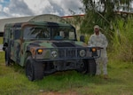 A member of the U.S. Space Force in a camouflaged uniform stands next to a Humvee in a tropical setting.