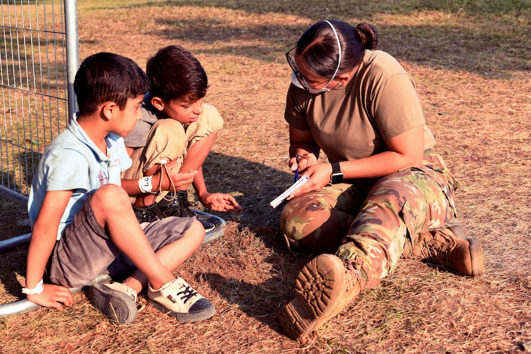 A service member sits on the ground with two boys and points at a paper.