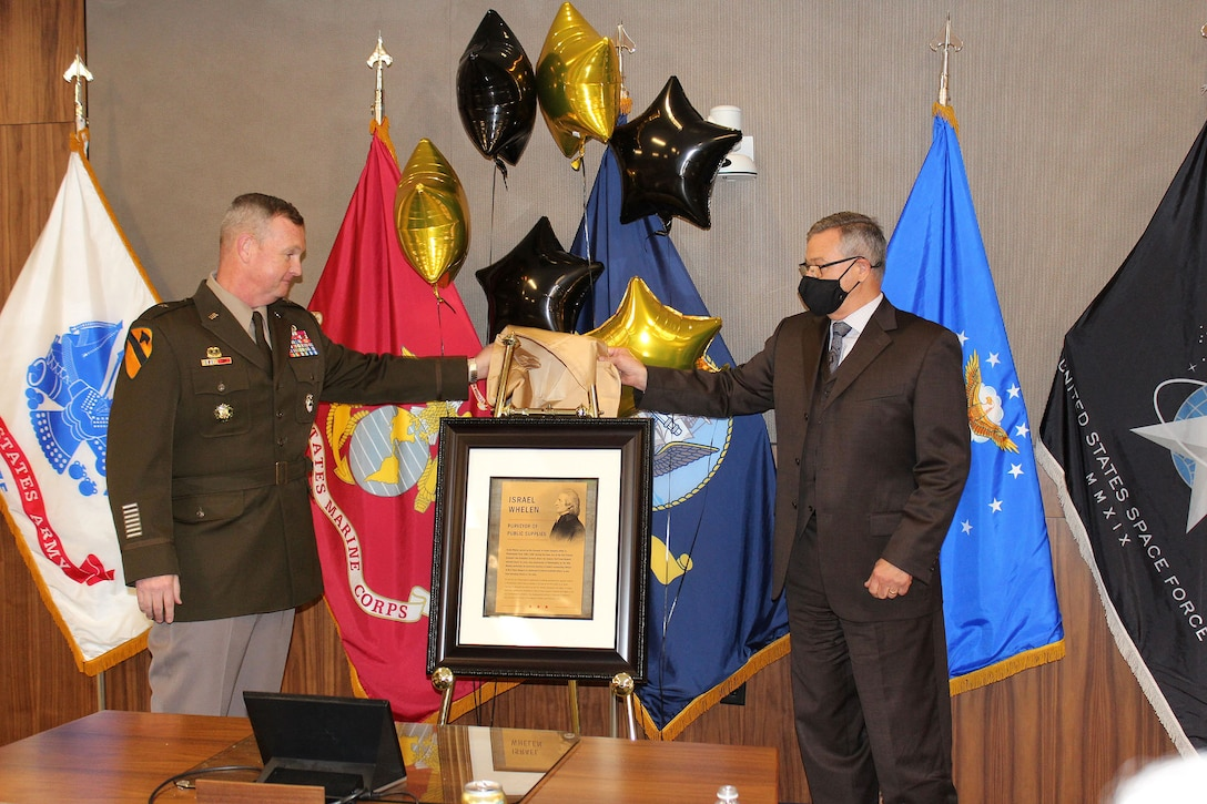 A soldier in Army dress greens stands to the left as he and a man in business attire jointly unveil a ceremonial image with flags of the United States and its military services in the background.