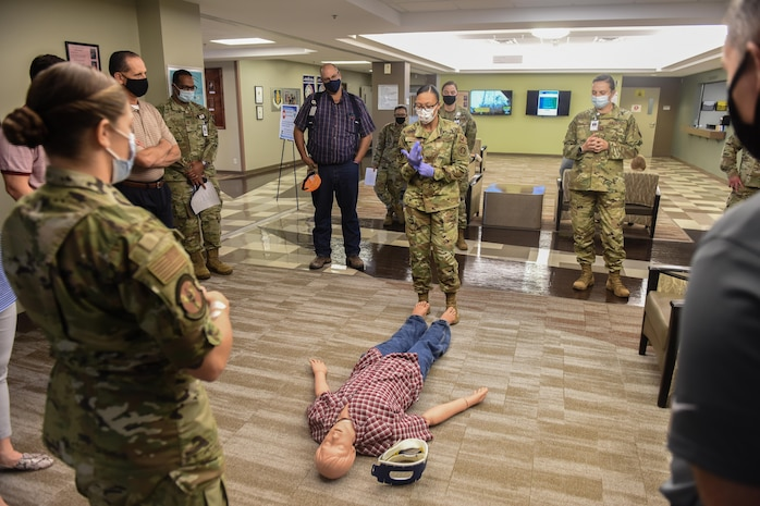 U.S. Air Force Staff Sgt. Katlyn Gorgus, foreground, and Airman 1st Class Ashleigh Chambers, center, both 97th Primary Care Flight aerospace medical technicians, show honorary commanders proper first aid procedures at Altus Air Force Base, Oklahoma, Sept .17, 2021. The 97th Primary Care Flight is responsible for the majority of primary care in the medical group and is divided into the Family Health, Pediatrics, Allergy and Immunizations Sections. (U.S. Air Force photo by 2nd Lt Cameron Silver)