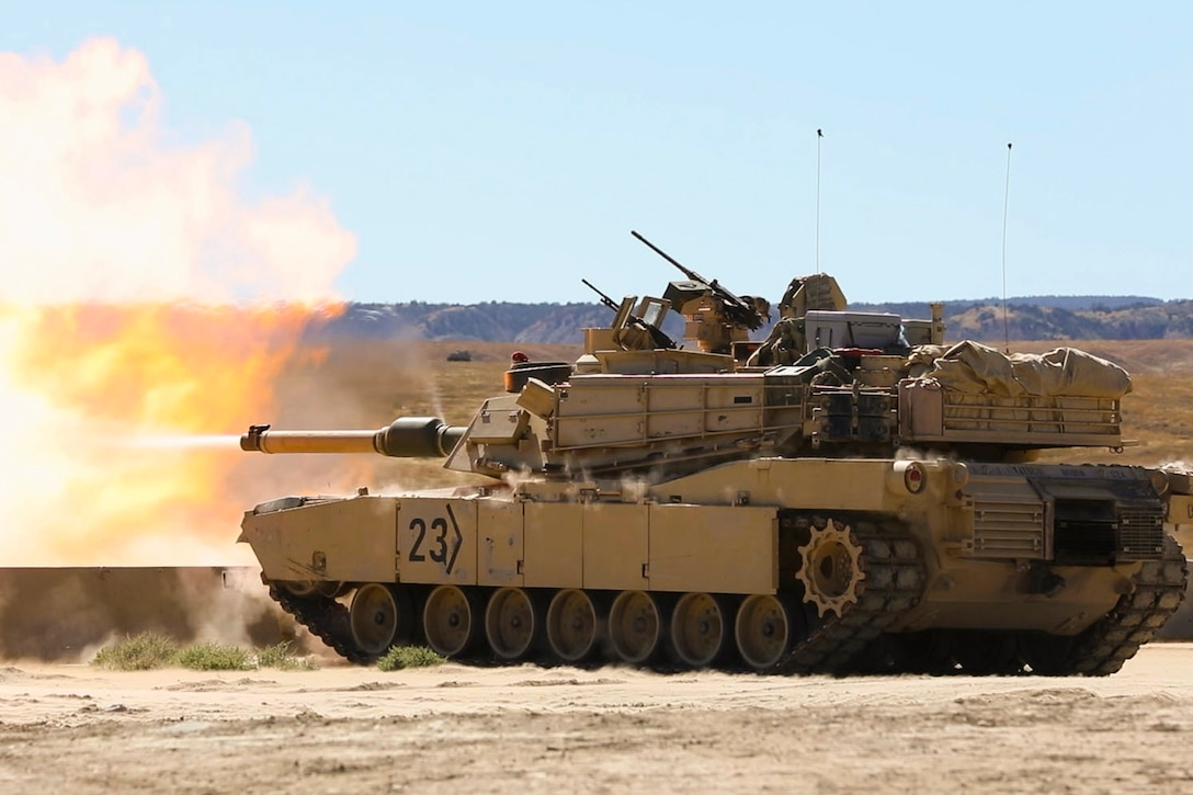 A tank fires rounds in a field.