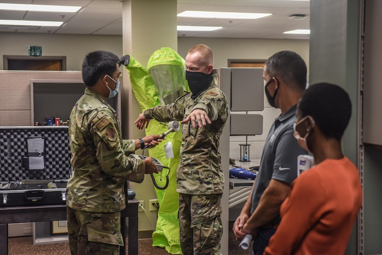 U.S. Air Force Airman 1st Class Angelo Dela Cruz, left, and Airman 1st Class Aidan Boterenbrood, right, both 97th Bioenvironmental Engineering Flight bioenvironmental engineering specialists, demonstrate to honorary commanders how they detect radiation at Altus Air Force Base, Oklahoma, Sept .17, 2021. The 97th Bioenvironmental Engineering Flight monitors 46 industrial shops, analyzes the drinking water quality, and manages the base radiation, electro and magnetic fields, and laser safety programs. (U.S. Air Force photo by 2nd Lt Cameron Silver)